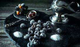 Still life in royal style. Frozen berry of blackberry with silver sugar bowl and spoon on black stone. Stand royalty free stock photography