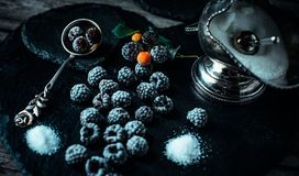 Still life in royal style. Frozen berry of blackberry with silver sugar bowl and spoon on black stone. Top view. Still life in royal style. Frozen berry of royalty free stock photo