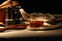 Still Life With Rum. Vintage still life with glass of rum near rope and old binoculars Stock Photo