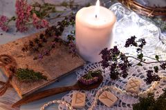 Still life with runes, healing herbs, witch diary, white candle and shining bottle on lace. Magic ritual. Wicca, esoteric and occult background with vintage stock images