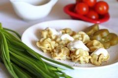 Still life: Russian pelmeni. Russian sour cream pelmeni and greens Stock Photo