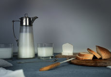 Still life. rustic dinner. milk jug, candles, tea, eggs, bread, rolls, cheese, on the table Royalty Free Stock Images