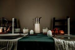 Still life. rustic dinner. milk jug, candles, tea, eggs, bread rolls on the table Stock Image
