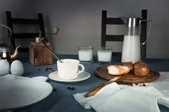 Still life. rustic dinner. milk jug, candles, tea, eggs, bread rolls on the table Royalty Free Stock Photo