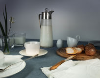 Still life. rustic dinner. milk jug, candles, tea, eggs, bread rolls on the table Royalty Free Stock Images