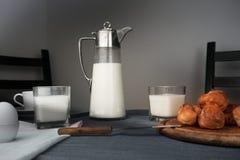 Still life. rustic dinner. milk jug, eggs, bread rolls on the table Royalty Free Stock Photography