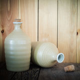Still life of sake bottles with light on wood background. Royalty Free Stock Image