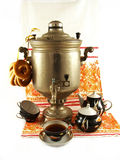Still life with samovar. Old samovar with bagels, a tea set and painted towel are on a white background Royalty Free Stock Photography