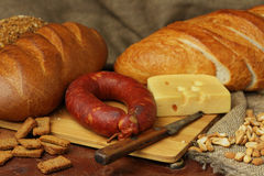 Still life with sausage, bread and cheese. Still life in rural style with sausage, bread and cheese in rural style Royalty Free Stock Photos
