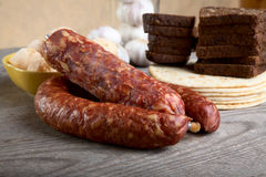 Still-life with sausage and bread on a  table Stock Images