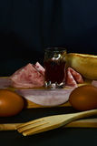 Still life with sausages. Wine, eggs and bread Stock Images