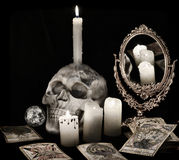 Still life with scary skull, burning candles and the tarot cards on black. Vintage still life with scary skull, mirror, burning candles and the tarot cards in royalty free stock image