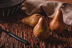 Still life scene of three pears, a paring knife, colander and towel on a woven twig background. royalty free stock images