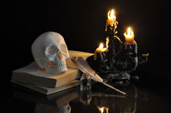 Still life with scull, books and melting candles Royalty Free Stock Photo