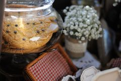 Still Life Set. Of glass jar, cookies, bouquet of flowers, box, blurred interior background Stock Photo