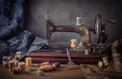 Still life with a sewing machine, scissors, threads. And cloth royalty free stock photo