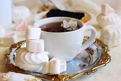 Still life shabby. Breakfast with a cup of tea and marshmallows on a silver tray in the foreground and a sandwich with black caviar in the background Royalty Free Stock Photo