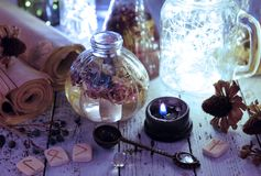 Still life with shining bottles, black candle and runes stock image