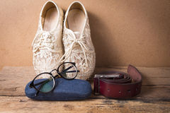 Still life of shoe with glasses and leather belt on wood Stock Photos