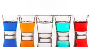 Five little glass with colored  beverages. Still life shoot of five five little glass with colored  beverages in a white background Stock Images