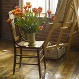 Still life shot of art studio. Interior view of artist studio with vase of flowers on a chair stock photography