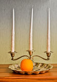 Still life: Silver candlestick and orange fruit Stock Images
