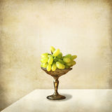 Still life, silver tray with grapes. A silver try with ripe grapes on a table in a well lit interior stock image
