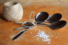 Still life:  simple subjects. Rope, sea salt and spoons on an old table Royalty Free Stock Photos