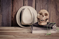 Still life - skull on books and hat on wooden table. Royalty Free Stock Photo