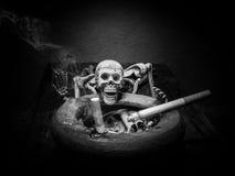 Still life skull and cigarette smoke. Black and white Stock Image