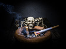 Still life skull and cigarette smoke. Royalty Free Stock Images