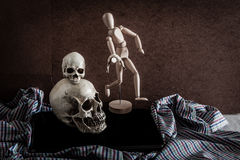Still life of skull,wooden figure, old vintage camera and notebo Royalty Free Stock Photography