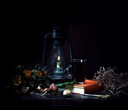 Still life. Small Dutch. kerosene lamp with a bouquet of roses and book on  wooden table   dark background Stock Photography