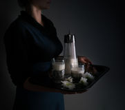 Still life in the small Dutch-style. a woman holding  tray with  pitcher of milk and cakes. vintage Royalty Free Stock Images