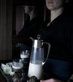 Still life in the small Dutch-style. a woman holding  tray with  pitcher of milk and cakes. vintage Stock Photo