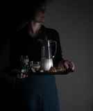 Still life in the small Dutch-style. a woman holding  tray with  pitcher of milk and cakes. vintage Royalty Free Stock Image