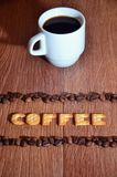 """English word """"Coffee"""", made up of salt cracker letters. Still life with a small white cup of hot coffee and a salt cracker in the form of letters stock images"""