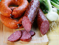 Still-life with smoked sausage and an onions Stock Photo