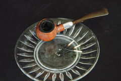 Still life, smoking pipe used on glass ashtray with black backgr Stock Photo