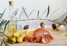 Still life with Spanish a pata negra ham, olives and olive oil in a bottle on a wooden cutting board. Royalty Free Stock Photography
