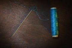 Still life- spool, thread, needle. Art still life- spool of thread, needle on a dark wooden background Stock Images