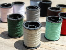 Still life of spools of thread on a wooden background Stock Photo