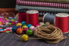 Still life of spools of thread. Still life of spools of thread,wooden beads and stack of colored fabrics Stock Photos
