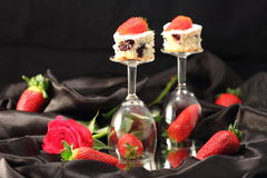 Still life: St. Valentine's Day. Rose, strawberry and cakes on glasses on black silk Stock Photos