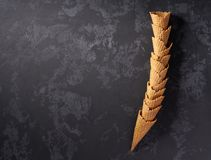 Still-life of stacked tower of empty waffle ice-cream cones on dark background, top view. Sweet waffle cones for ice cream  concept on dark background, top view stock photos