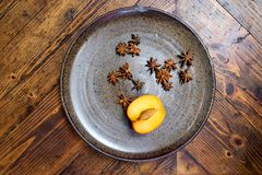 Still life of star anise spice and a half peach on a rustic circ Royalty Free Stock Photography