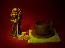 Still life with a statuette of the god of tea, a cup and lumps o Stock Photography