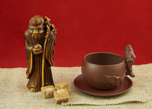 Still life with a statuette of the god of tea, a cup and lumps o Stock Image