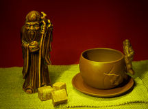 Still life with a statuette of the god of tea, a cup and lumps o Stock Photos