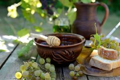 Still life. With honey, grapes and white bread royalty free stock photography